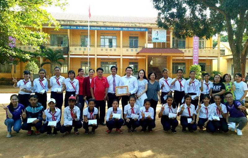 Đại diện nhà tài trợ và chính quyền địa phương huyện Cư M'gar chụp ảnh lưu niệm cùng các học sinh được tặng học bổng của Trường THCS Cao Bá Quát